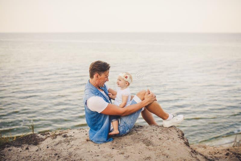 Familjsommarsemester i natur fadern och den lilla dottern sitter på den sandiga klippan för ett år med den höga sikten av havet E arkivbild