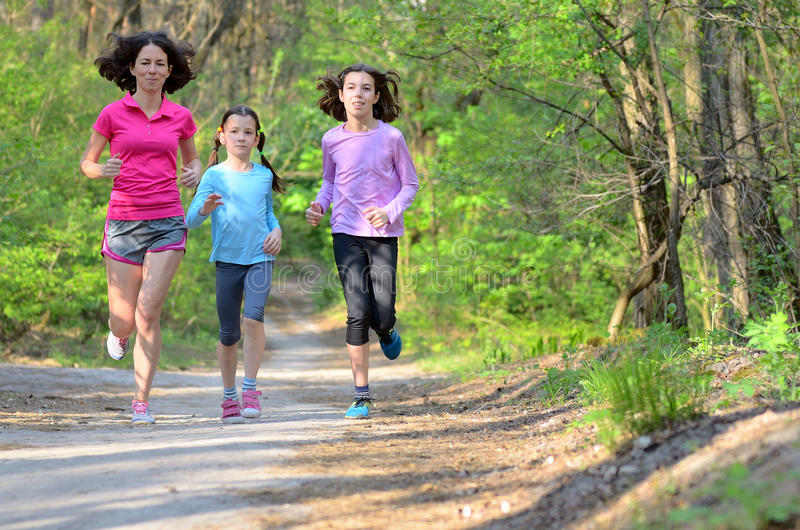 Familjsport, lycklig aktiv moder och ungar jogga som kör i skog royaltyfri fotografi