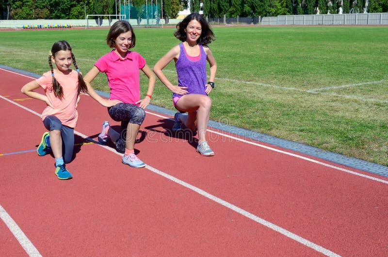 Familjsport och kondition, lycklig moder och ungar som utomhus övar och kör på stadionspår, aktiva barn royaltyfri foto