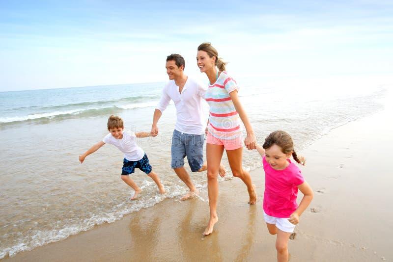 Familjspring på en sandig strand royaltyfri foto