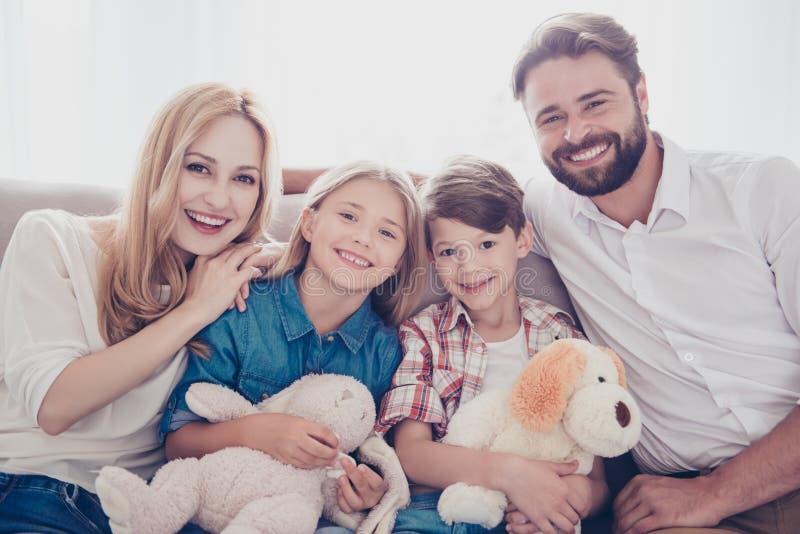 Familjstående av fyra Lyckliga föräldrar och deras gladlynta ungar b arkivfoto