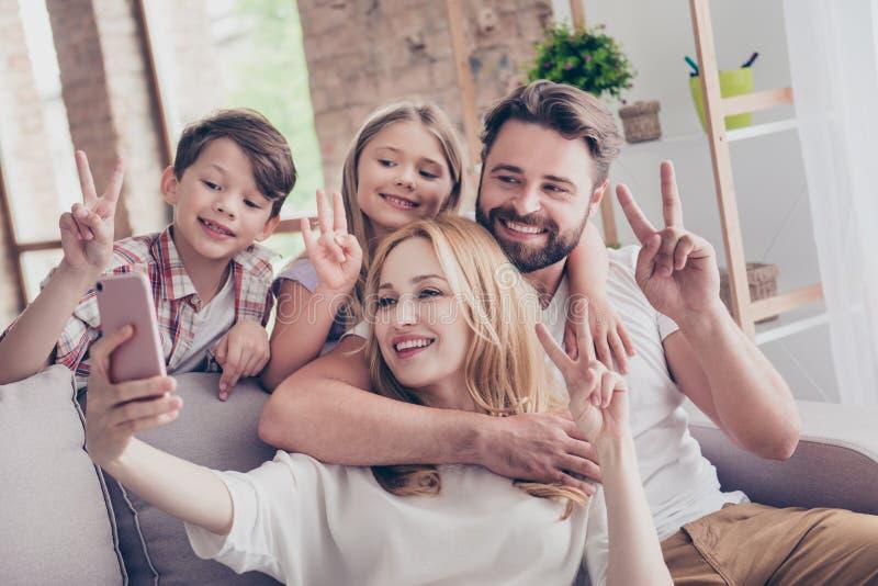 Familjstående av fyra som visar fredtecken Lyckliga föräldrar och arkivfoto