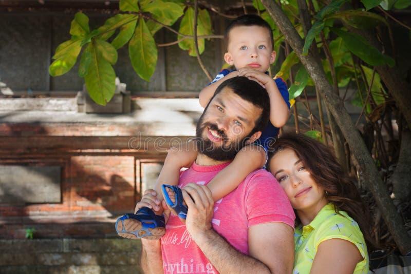 Familjstående - den lyckliga modern, faderinnehav behandla som ett barn sonen på skuldror royaltyfri fotografi