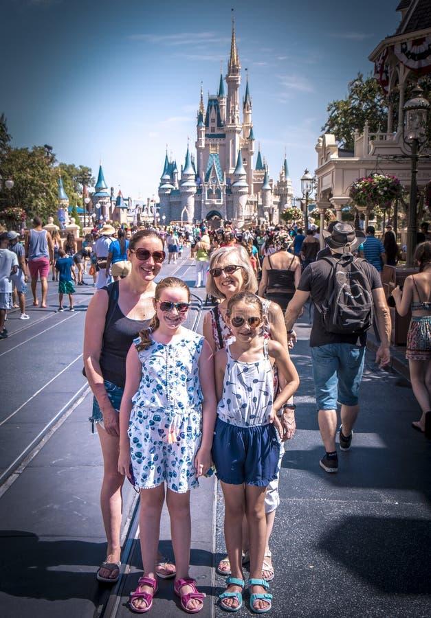 Familjstående framme av den Cinderella prinsessaslotten på den Disney världen Florida arkivfoton