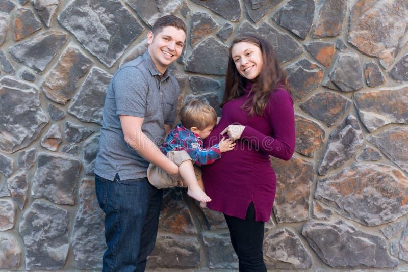 Familjstående med ett litet barn som kysser en buk för gravid kvinna` s royaltyfri foto
