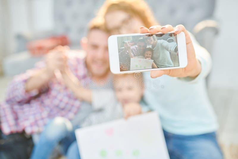 Familjstående på den Smartphone skärmen royaltyfri foto