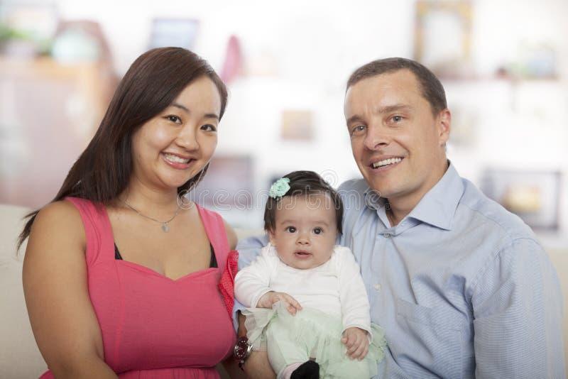 Familjståendemoder, dotter, fadersammanträde på soffan royaltyfria foton