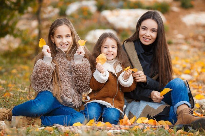 Familjståenden av systrar i gul höst parkerar royaltyfri fotografi