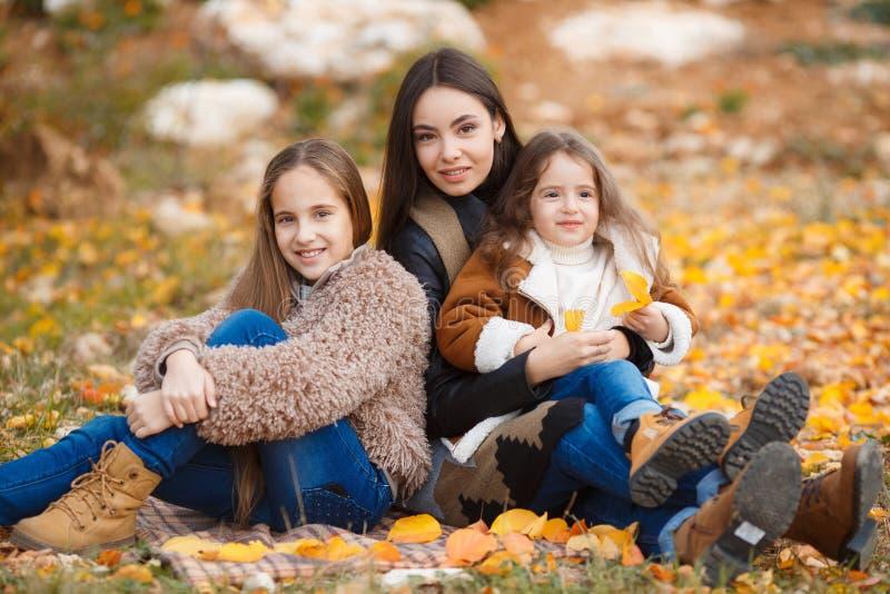 Familjståenden av systrar i gul höst parkerar arkivfoto