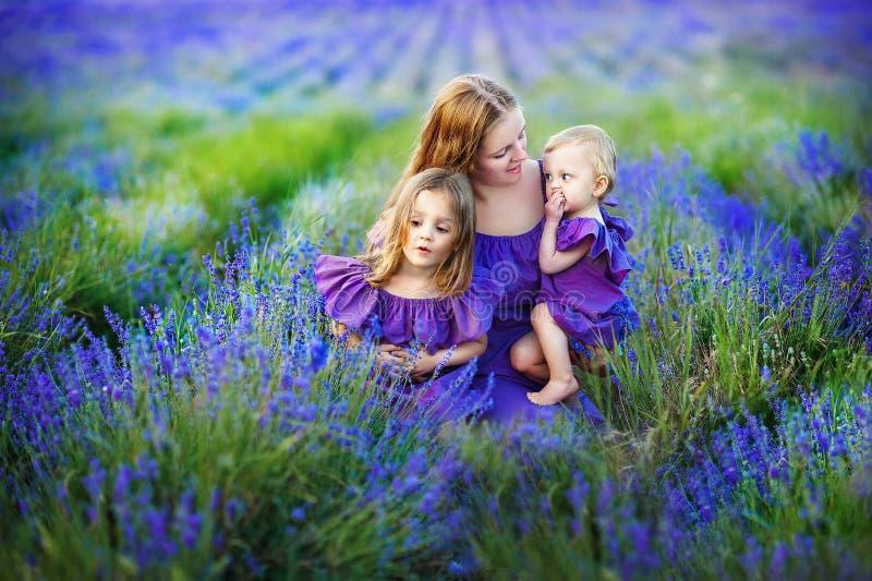 Familjståenden - fostra och två döttrar i ett härligt lavendelgolv Begrepp av en stark härlig familj royaltyfri bild