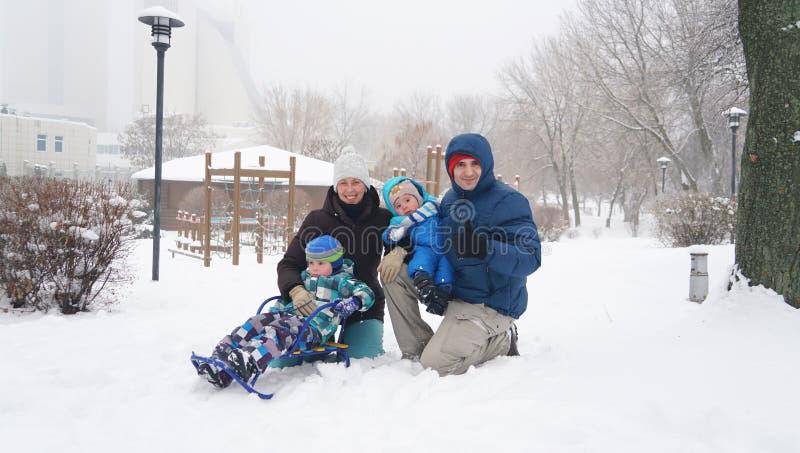 Familjståenden i vintern parkerar charmiga ungar royaltyfri foto