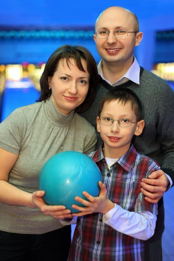 Familjstand tillsammans med och hållboll för bowling royaltyfri bild