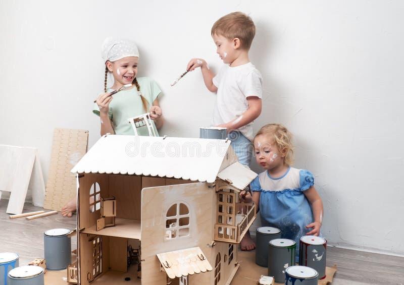 Familjtid: Barn målar ett leksakhus som göras av kryssfaner för dockor i vit fotografering för bildbyråer