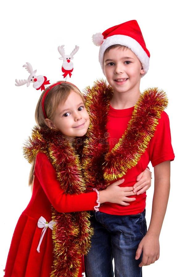Familjtid, nytt års glitter Lycklig broder med den santa hatten på hans huvud och en syster med hjorthorn som kramar varje arkivfoton