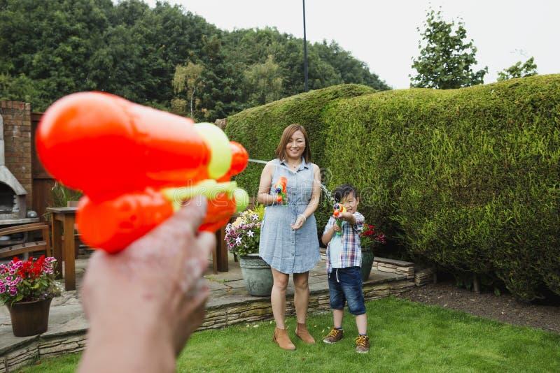 Familjvattenkamp i trädgården arkivfoto