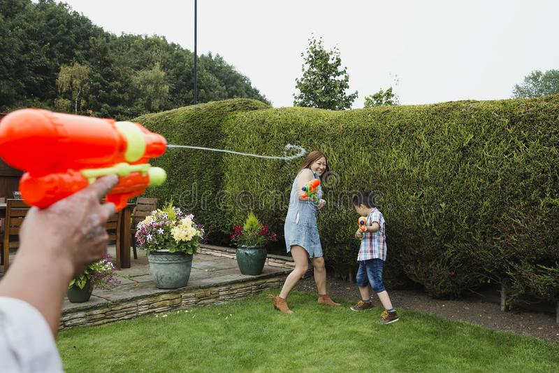 Familjvattenkamp i trädgården arkivfoton
