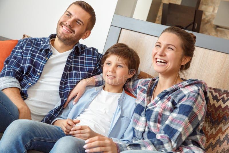 Famille à la maison s'asseyant sur le sofa dans le salon observant ensemble la comédie à la TV riant le plan rapproché gai photo stock