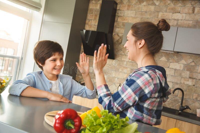 Famille à la maison se tenant dans la cuisine donnant ensemble la vue de côté haut cinq gaie riante photo libre de droits
