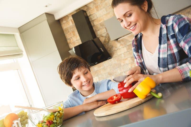 Famille à la maison se tenant dans le fils de cuisine ensemble regardant la mère coupant des légumes joyeux photographie stock