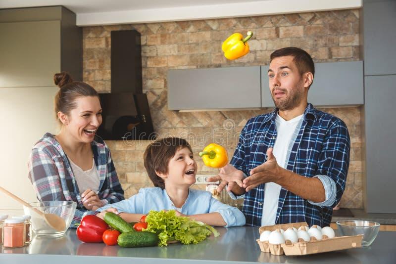 Famille à la maison se tenant dans la mère et le fils de cuisine ensemble regardant rire de jonglerie de père joyeux photo libre de droits