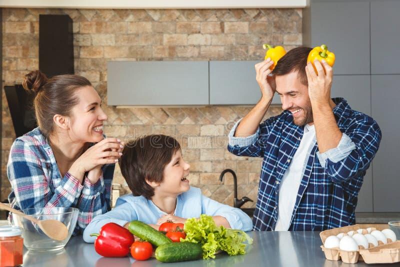 Famille à la maison se tenant dans la mère et le fils de cuisine ensemble riant du père jouant avec des paprikas image libre de droits