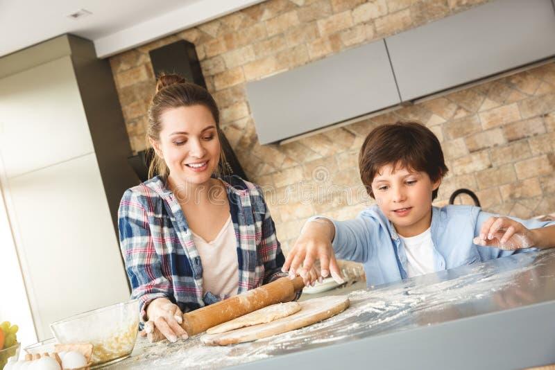 Famille à la maison se tenant à la table dans le fils de cuisine ensemble jouant avec de la farine tandis que pâte de roulement d image stock