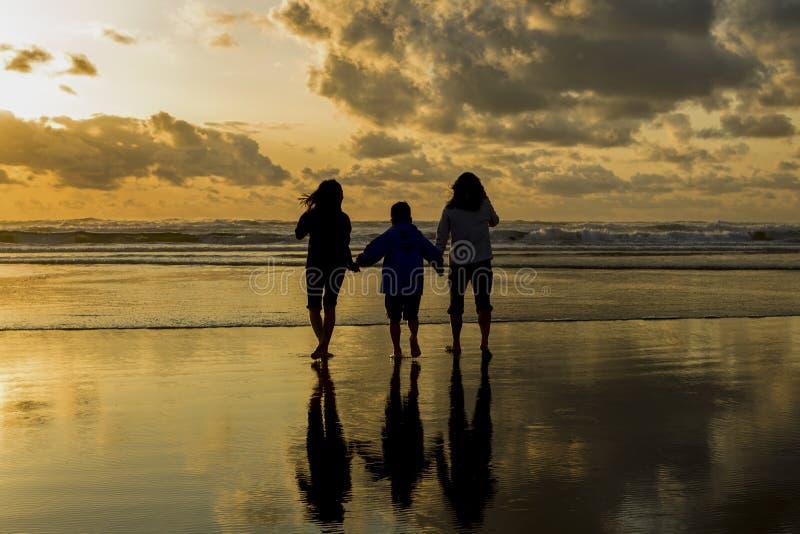 Famille à la plage au coucher du soleil photo libre de droits