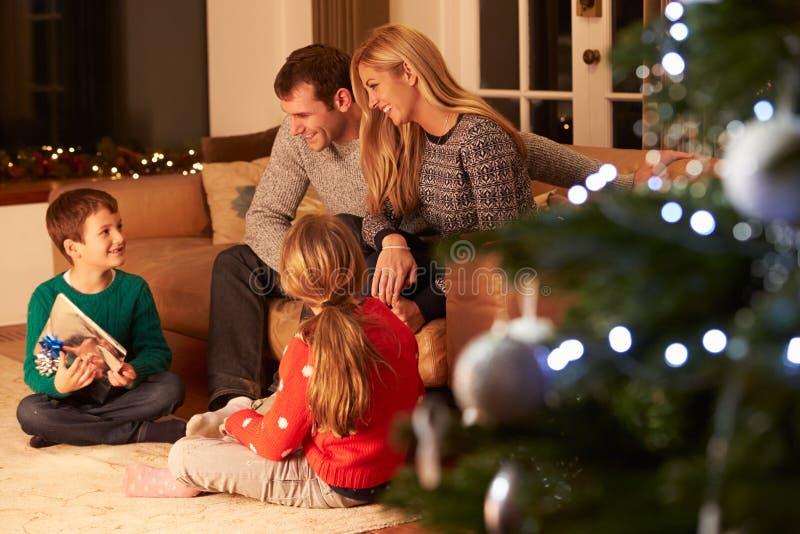 Famille échangeant des cadeaux par l'arbre de Noël photographie stock libre de droits
