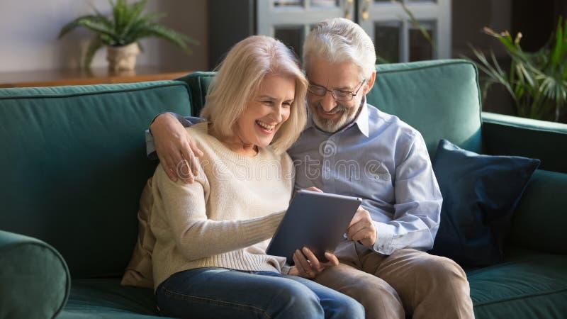 Famille, épouse et mari mûrs heureux à l'aide du comprimé à la maison ensemble image stock