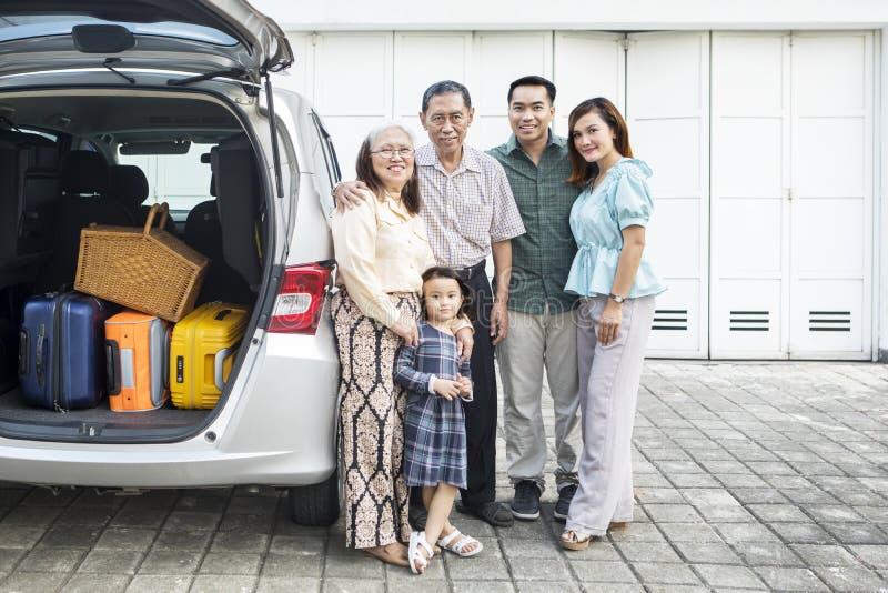 Famille étendu avec la voiture dans le garage de maison photos stock