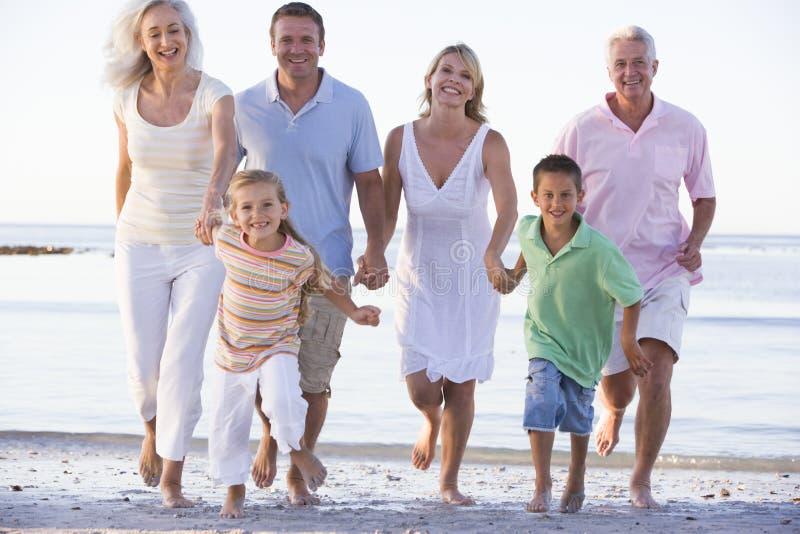 Famille étendu marchant sur la plage photo stock