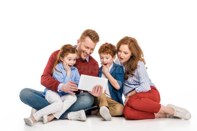 famille étonnée avec deux enfants utilisant le comprimé numérique ensemble photographie stock libre de droits