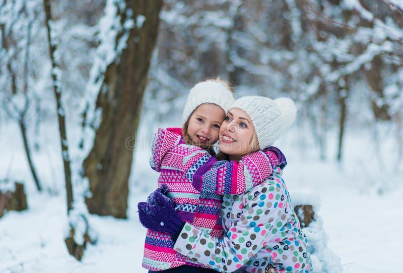 Famille étreignant et riant sur la promenade neigeuse d'hiver en nature images libres de droits