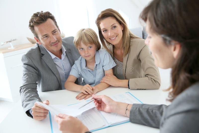 Famille achetant la nouvelle maison dans l'agence immobilière images stock