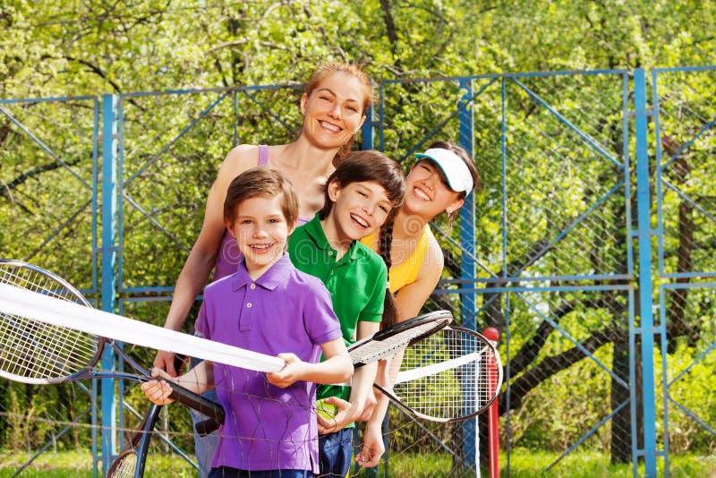 Famille active ayant l'amusement jouant le tennis photographie stock