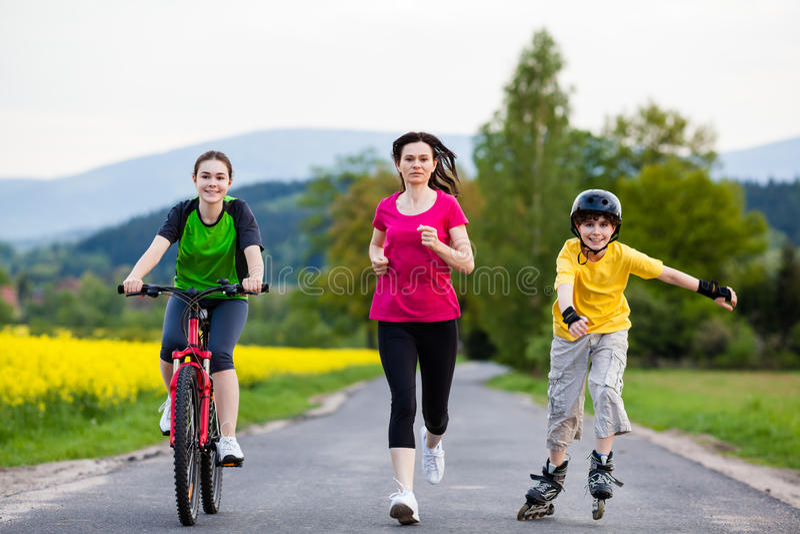 Famille active - mère et enfants courant, faire du vélo, faisant du roller photographie stock
