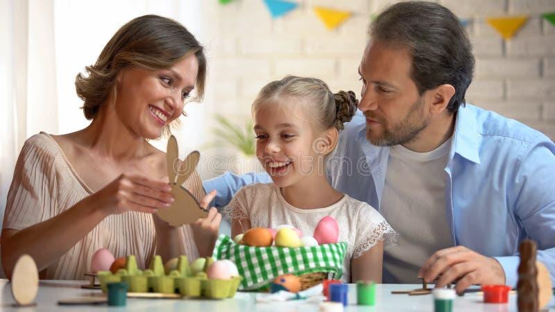 Famille admirant le jouet en bois dans la forme du lapin, symbole de Pâques, décoration faite main photographie stock libre de droits