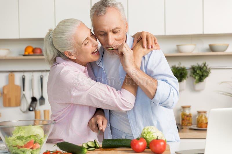 Famille affectueuse drôle mûre de couples utilisant l'ordinateur portable et la salade de cuisson photographie stock