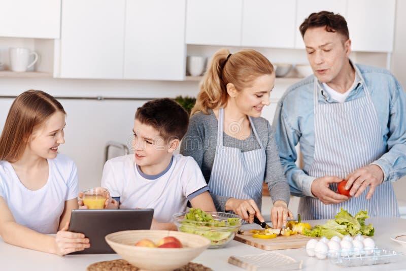 Famille affectueuse gaie faisant cuire le dîner ensemble images stock