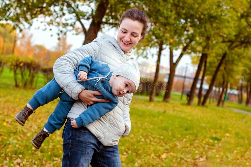Famille affectueuse heureuse en parc Mère dans le blanc et bébé garçon dans le bleu ayant l'amusement, jouant et riant en nature image stock