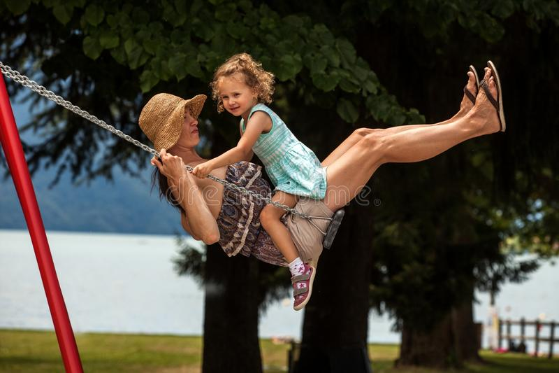 Famille affectueuse heureuse ! Jeune mère et sa fille d'enfant balançant sur les oscillations et riant une soirée d'été dehors, b photographie stock libre de droits