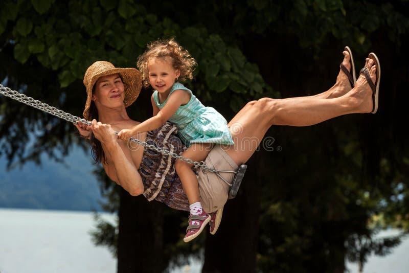 Famille affectueuse heureuse ! Jeune mère et sa fille d'enfant balançant sur les oscillations et riant une soirée d'été dehors, b images libres de droits