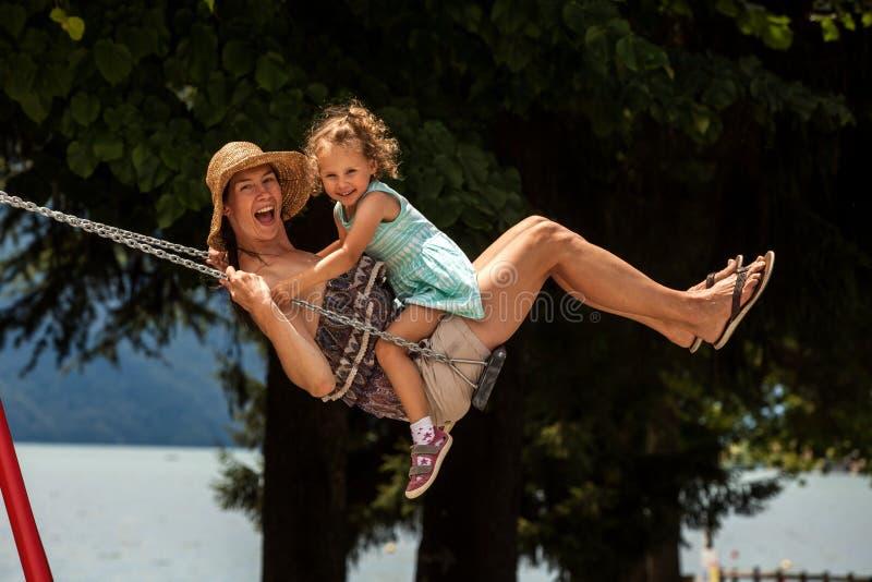 Famille affectueuse heureuse ! Jeune mère et sa fille d'enfant balançant sur les oscillations et riant une soirée d'été dehors, b image stock