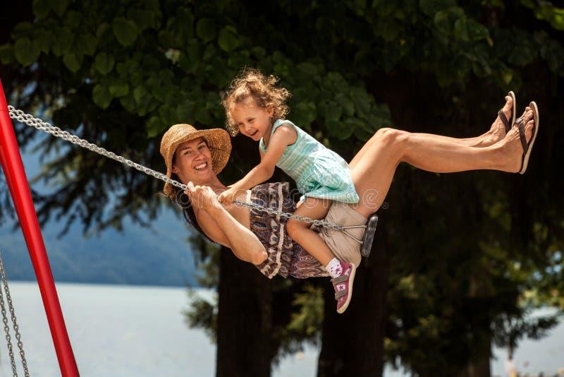 Famille affectueuse heureuse ! Jeune mère et sa fille d'enfant balançant sur les oscillations et riant une soirée d'été dehors, b photo libre de droits