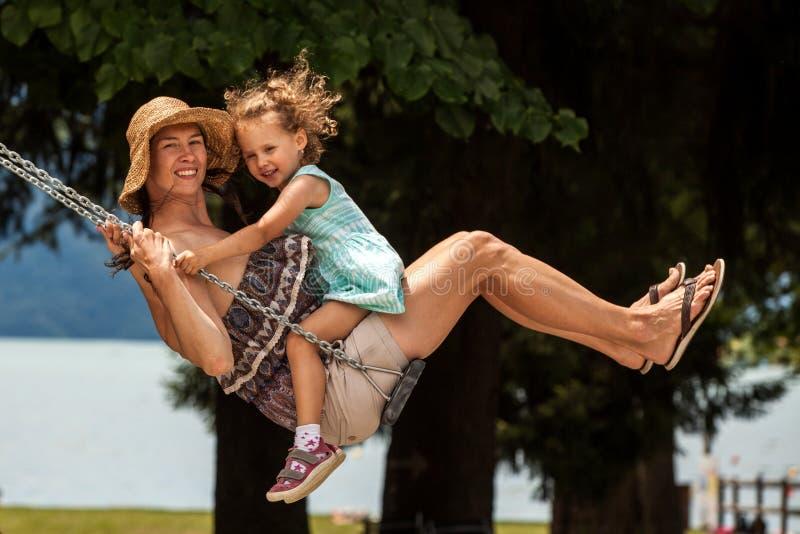 Famille affectueuse heureuse ! Jeune mère et sa fille d'enfant balançant sur les oscillations et riant une soirée d'été dehors, b photographie stock