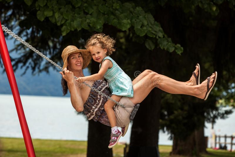 Famille affectueuse heureuse ! Jeune mère et sa fille d'enfant balançant sur les oscillations et riant une soirée d'été dehors, b photo stock