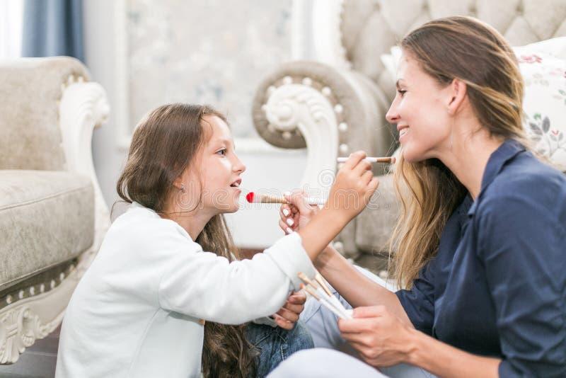 Famille affectueuse heureuse La mère et la fille font des cheveux, manucures, font votre maquillage et ont l'amusement images libres de droits