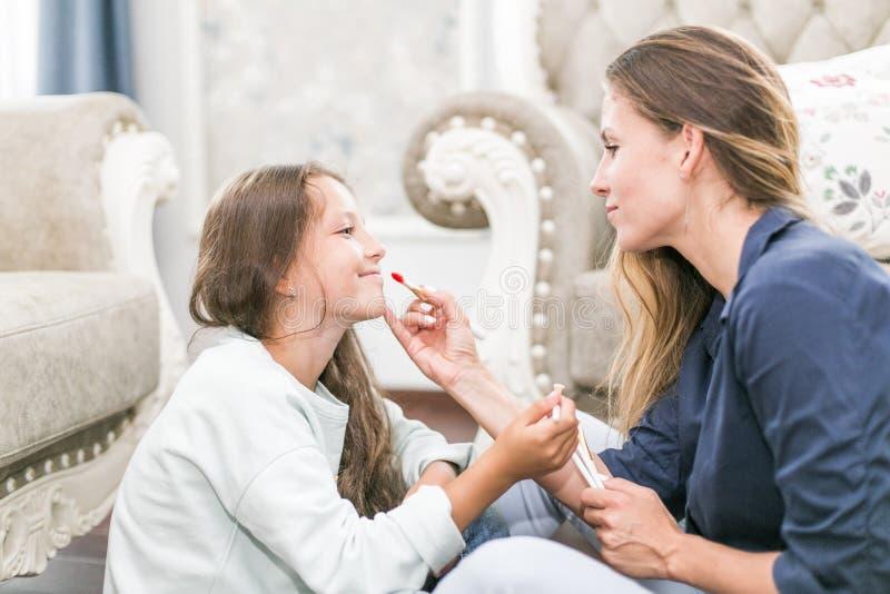 Famille affectueuse heureuse La mère et la fille font des cheveux, manucures, font votre maquillage et ont l'amusement photos libres de droits