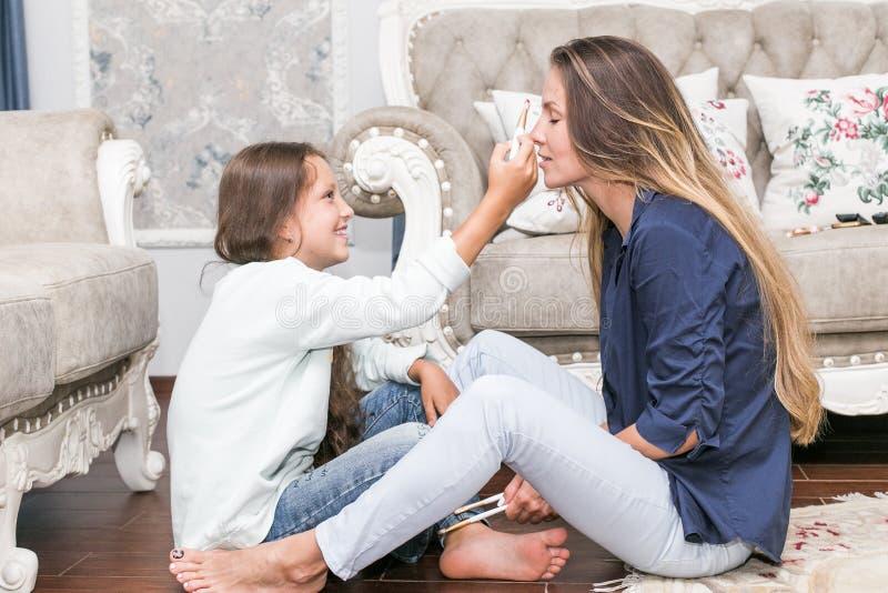 Famille affectueuse heureuse La mère et la fille font des cheveux, manucures, font votre maquillage et ont l'amusement photographie stock libre de droits
