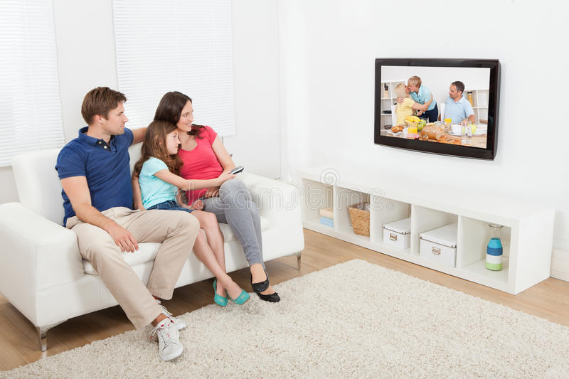 Famille affectueuse regardant la TV photos stock